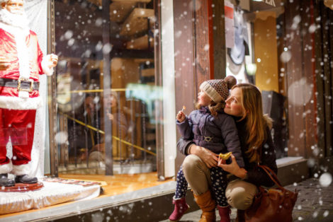 64888685 - little toddler girl with mother on christmas market. funny happy kid making window shopping with santa claus. holidays, christmas, childhood and people concept. family during winter snowfall