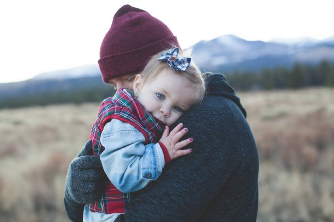 child being held close by parent