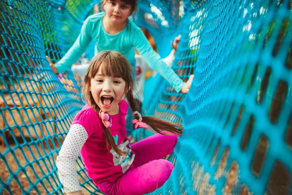 Girl climbing playground ropes